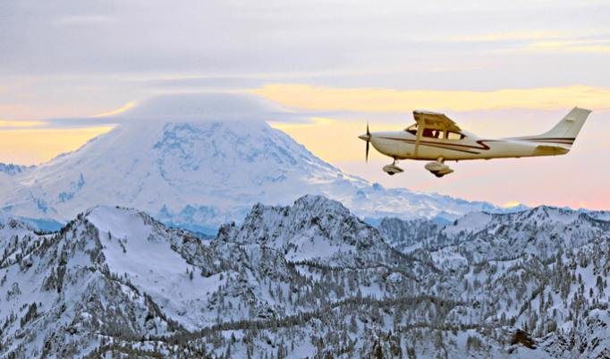 Flugzeug vor schneebedecktem Berg
